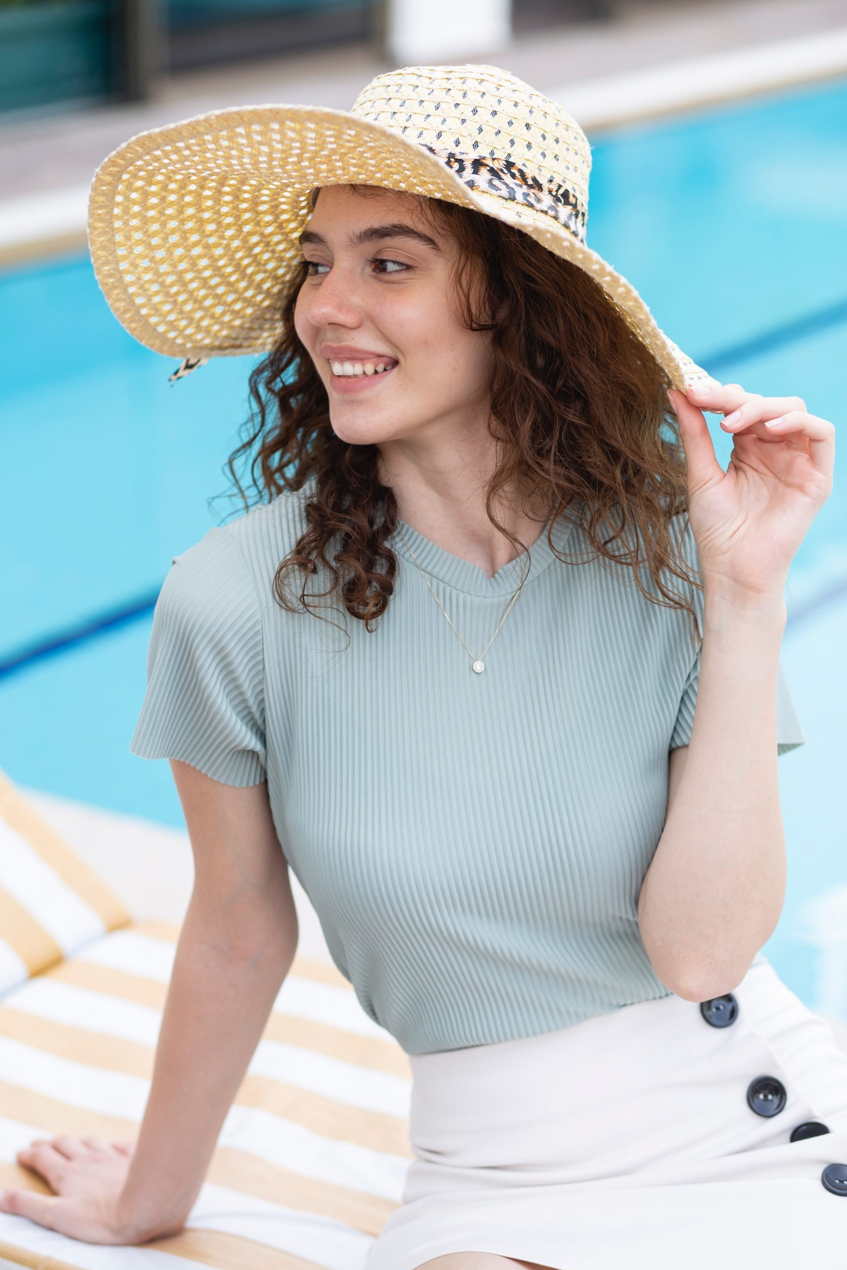woman in white and blue striped dress wearing brown straw hat